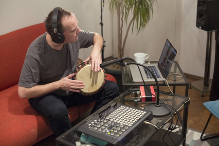 Professional musician recording djembe drum instrument in digital studio at home. He is surrounded with instruments and midi controller. Music production concept.