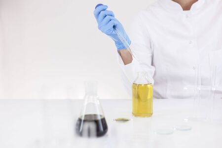 Closeup of a female scientist in a laboratory working with cbd oil extracted from a marijuana plant using a glass dropper,tubes and a bowl.Healthcare pharmacy medical cannabis.