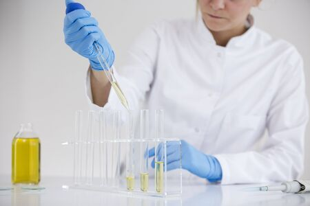 Female scientist in a laboratory working with cbd oil extracted from a marijuana plant. She is waring blue glows and glasses, and using a glass dropper, tubes and a bowl for the experiment.