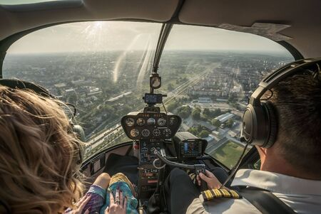 Portrait of beautiful blonde women and pilot enjoying helicopter flight. She is amazed by cityscape and wearing pilot headphones.