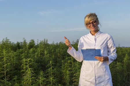 Scientist on marijuana field happy and satisfied with CBD hemp plants. She is smiling