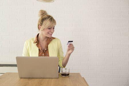 Donna eccitata felice che utilizza carta di credito e laptop per lo shopping online. È seduta a tavola a casa.