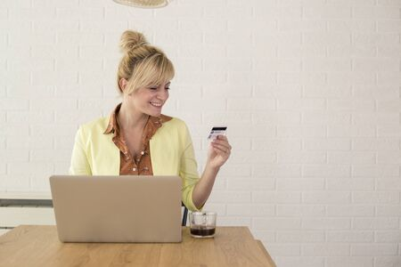 Happy excited woman using credit card and laptop for online shopping. She is sitting at table at home.