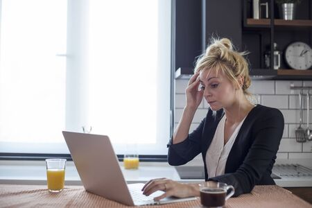 Young woman having headache while working on laptop. She is sitting at her kitchen table at home.