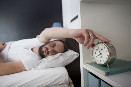 Man waking up in his bedroom and stopping alarm clock. It's morning. Stock Photo