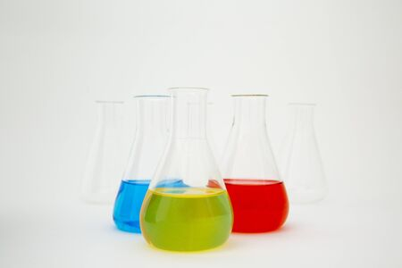 Scientific laboratory glass erlenmeyer flask filled with blue, yellow and red liquid on white background. Zdjęcie Seryjne