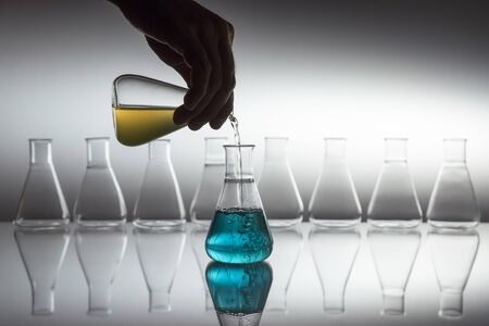 Hand pouring yellow in to blue liquid in scientific laboratory glass erlenmeyer flask with glassware equipment on reflective surface.