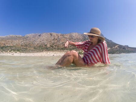 Happy woman with straw hat enjoying on sun in shallow sea water on the Balos beach. Crete Greece. Standard-Bild - 143138387