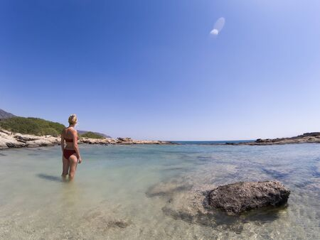 Back view of woman In bikini standing in shallow sea water on Elafonissi beach, Crete Greece Standard-Bild - 143138430