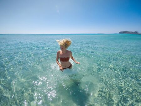 Free happy woman in a bikini jumping in shallow turquoise water by the beach on Crete island. Standard-Bild - 143138418