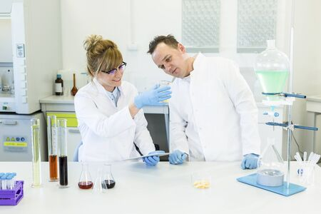 Scientists working with terpene crystals called terpsolate. They are in pharmaceutical laboratory and CBD and CBDa oils are on table in glass tubes and erlenmeyer flasks. Healthcare from cannabis.