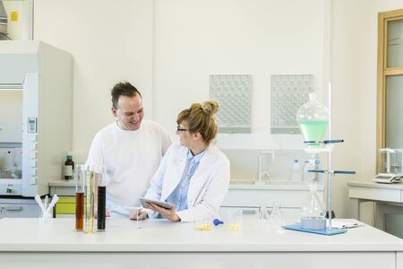 Male and female scientists working with tablet in pharmaceutical laboratory. They are focused on CBD and CBDa extracts in oil and crystal form. Glass tubes, erlenmeyer flasks and separatory funnel are part of laboratory equipment on table.