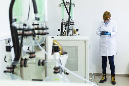 Scientist typing on black tablet in laboratory during CBDa oil extraction. She wears rubber gloves and stands next to rotational vaporizer with green condenser called rotavapor.