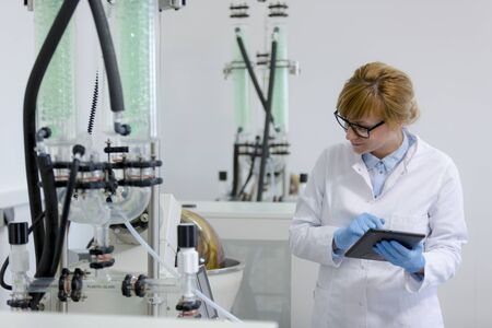 Scientist with tablet operating rotational vaporizer with green condenser. She wears latex gloves and glasses. CBD hemp oil extraction is in rotational flask.