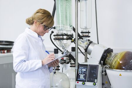 Scientist holding paper board and controlling rotational vaporizer during CBD oil extraction. Machine has green condenser and rotational flask where CBD hemp oil extraction is in process.