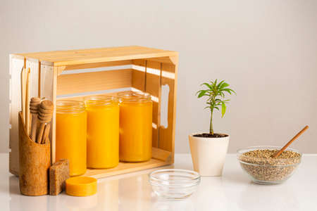 Three jars of CBD honey placed in a wooden crate. Around the crate are positioned a marijuana plant in a white flowerpot, a bowl with hemp seeds, wooden spoons for honey, as well as several CBD products in the form of soap.