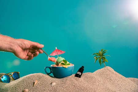 Ice cream in a cup, a drop of CBD oil and a twig of marijuana in the sand. On the side are sunglasses, ice cream decorations, seashells. In the frame is a hand taking ice cream with a spoon. Фото со стока
