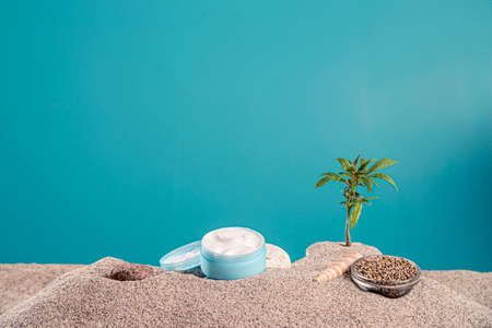 Sunscreen from CBD products and twigs of the marijuana plant in the sand. Around the product you can also see a bowl with hemp seeds, sunglasses, sea shells, stone and the packaging itself.