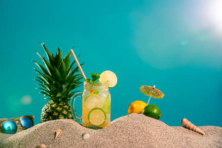 Lemonade in different glasses / jars, CBD dropper oil and a twig of marijuana plant in the sand. Sunglasses and seashells can be seen from the side. The background is half in the sand, half in blue colour.