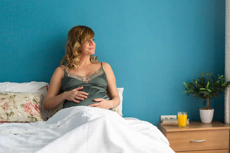 A smiling pregnant woman in a semi-sitting position in bed with her hands around her stomach. On some shots, she's looking out the window.