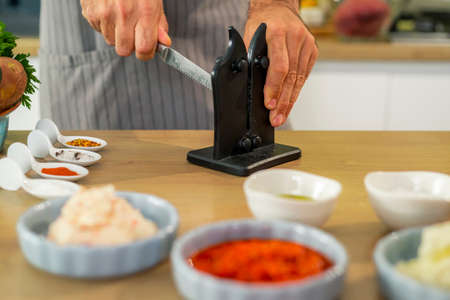 The chef sharpens the knives before preparing a meal in the kitchen. In the foreground are his two hands, as well as vegetables, spices and small kitchen bowls around on the work surface.