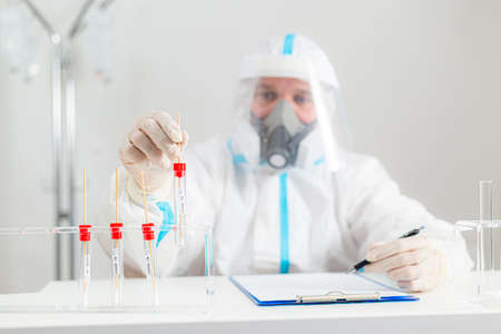 Medical worker in PPE working with COVID-19 test in hospital lab, writing down the results.