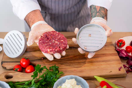 Close up of a photographed hand of a chef showing a ready raw burger just taken out of a shaping press. Vegetables and primrose leaves can be seen around the kitchen wooden board.