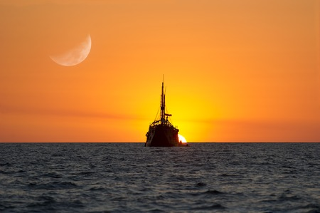 The sun sets while the moon rises beyond a ship at sea  photo