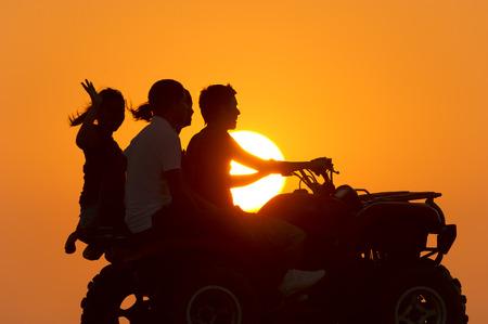 quad: Four people having fun riding a quad at sunset.