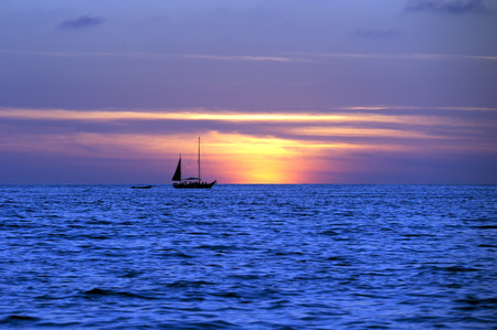 A Sailboat is silhouetted against a vivid sunset sky. photo