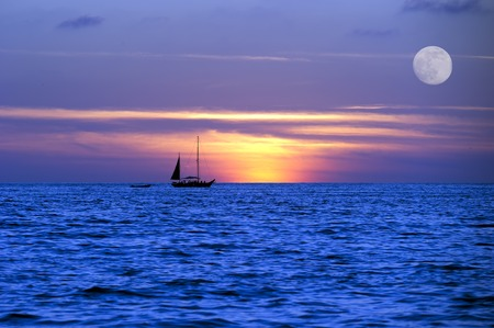 A sailboat moves across the ocean on its journey photo