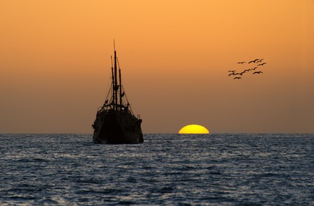 An old wooden pirate ship sits on the water with the colorful cloudscape sunset above.