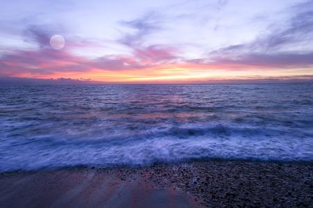 Moon rises over a colorful moon ocean beach sunset.