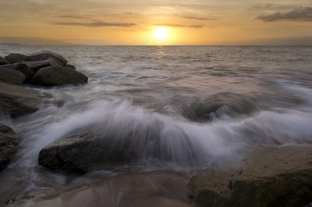 breaks: An ocean beach wave breaks on the sand and rocks as the sun sets in the colorful sky. Stock Photo