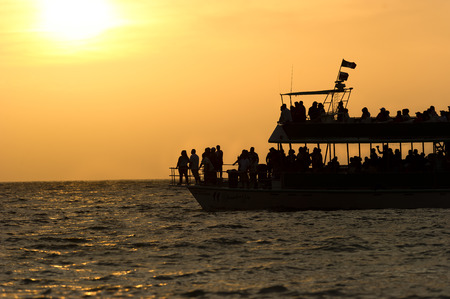 ferryboat: Ferry Boat Sihouette with passengers at sunset.
