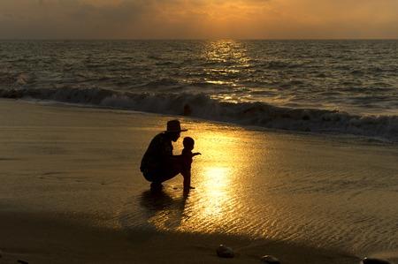 padre e hija: Padre y beb� en la playa en silueta contra el sandsand el oc�ano Foto de archivo