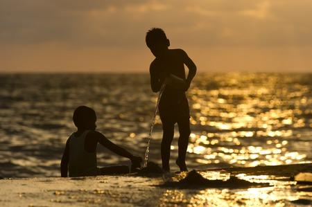 シルエット水とビーチで遊んでいる子供たち。