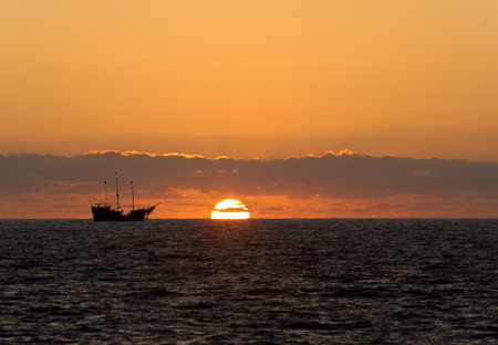 ship: Pirate ship sunset  is sailing at sea silhouetted against a setting sun and a colorful cloudy filled sky.