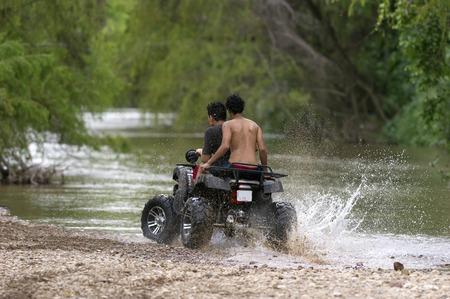 四輪バギー ATV は、水や川の端に汚れが飛散しながら刺激的な乗車を持つ若いライダーのカップルです。