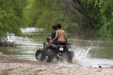 Quad bike ATV is a couple of young riders having an exciting ride while splashing water and dirt at the edge of the river.