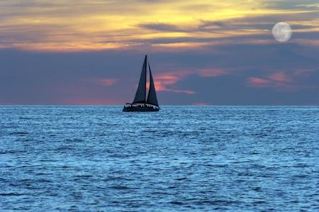 Żaglówka sylwetka jachtu jest poruszające się w wodzie o zachodzie słońca z pełni księżyca wschodzącego w chmurze wypełnione niebo.