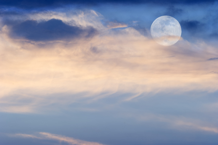 Moon clouds is a soft colorful scenic cloudscape against a blue sky with the full moon rising in a blue sky as it sits behind some wispy colorful clouds.