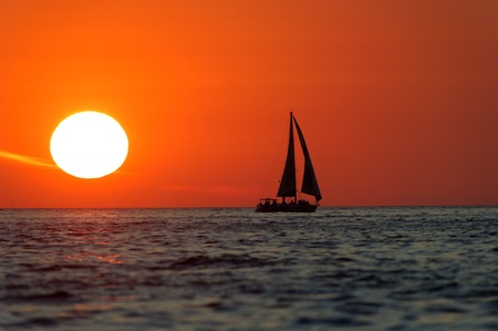 sailboat: Sailboat Sunset is sailboat silhouetted a bright red sky with a bright white burning sun setting in the background. Stock Photo