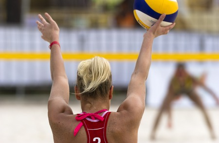 volleyball serve: Volleyball player is a female athlete volley ball player getting ready to serve the ball.