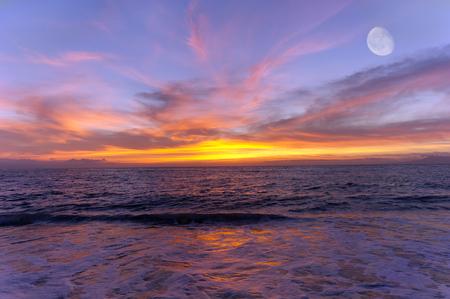 海サンセット月は空に高い上昇 4 分の 3 月に海の上いっぱいカラフルな雲空です。 写真素材