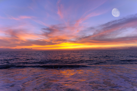 Ocean sunset moon is a colorful cloud filled sky over the ocean with a three quarter moon rising high in the sky.
