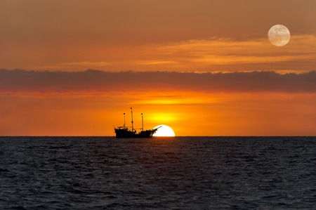 pirate ship: Ship silhouette sunset is an old wooden pirate ship sitting at sea with the full moon rising in the sunset sky.