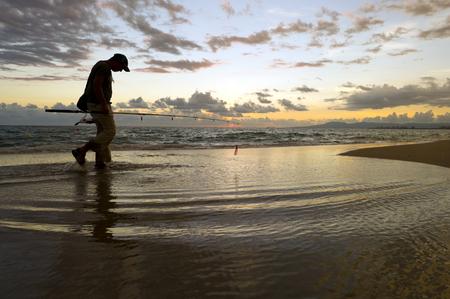 pescador: Playa de los pescadores es un pescador caminando por la playa al amanecer en silueta contra el cielo nubes y el aumento del sol de la mañana.