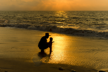 Father baby is a silhouette father showing his child the wonder of the ocean for the very first time.