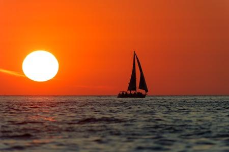 ヨット日没は、ヨットは、夕日を背景に燃える明るい白と明るい赤い空をシルエットです。